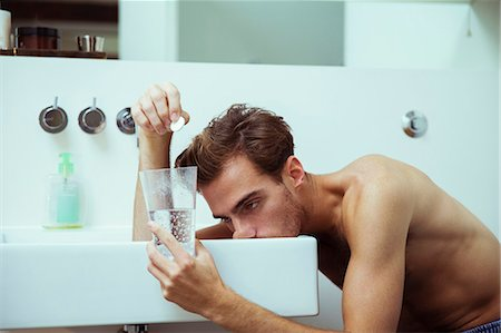 Hungover man watching effervescent tablets in bathroom Stock Photo - Premium Royalty-Free, Code: 6113-07543010