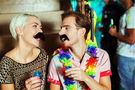 Couple wearing fake mustaches at party Stock Photo - Premium Royalty-Free, Code: 6113-07543030