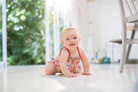 Baby girl crawling on kitchen floor Stock Photo - Premium Royalty-Free, Code: 6113-07543143