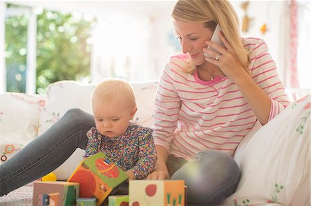 Mother with baby girl talking on cell phone Stock Photo - Premium Royalty-Free, Code: 6113-07543157