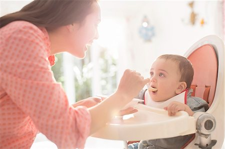 Mother feeding baby boy in high chair Stock Photo - Premium Royalty-Free, Code: 6113-07543155