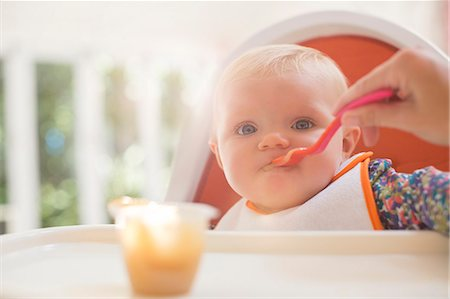 Mother feeding baby girl in high chair Stock Photo - Premium Royalty-Free, Code: 6113-07543241