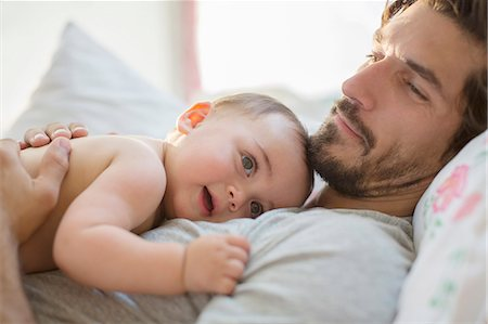 Father laying with baby boy on bed Stock Photo - Premium Royalty-Free, Code: 6113-07543250