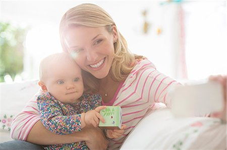 Mother taking self-portrait with baby girl Stock Photo - Premium Royalty-Free, Code: 6113-07543283
