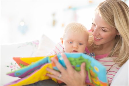 Mother reading to baby girl on sofa Stock Photo - Premium Royalty-Free, Code: 6113-07543284