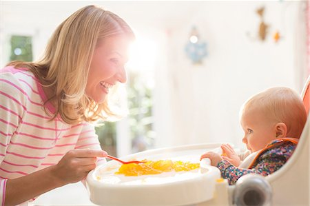 Mother feeding baby girl in high chair Stock Photo - Premium Royalty-Free, Code: 6113-07543224