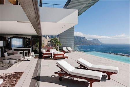 Modern patio and infinity pool overlooking ocean Stock Photo - Premium Royalty-Free, Code: 6113-07543356