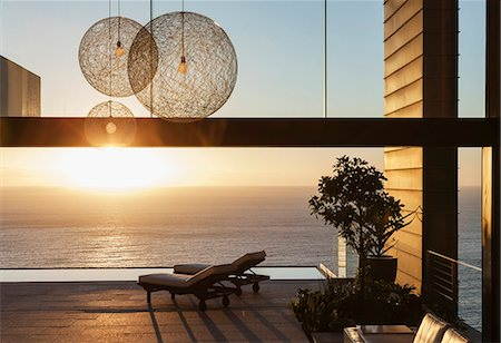 domestic - Patio of modern house overlooking ocean at sunset Stock Photo - Premium Royalty-Free, Code: 6113-07543372
