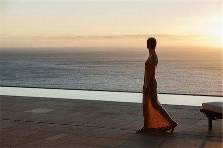 Woman looking at ocean from modern patio at sunset Stock Photo - Premium Royalty-Free, Code: 6113-07543383