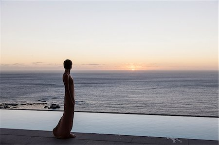 Woman looking at ocean from patio Stock Photo - Premium Royalty-Free, Code: 6113-07543385