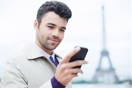 Businessman using cell phone by Eiffel Tower, Paris, France Stock Photo - Premium Royalty-Free, Code: 6113-07543392