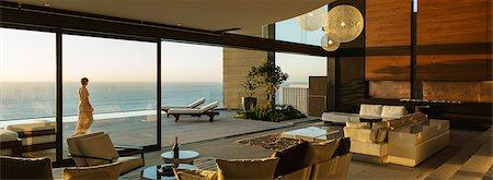 Woman walking on modern patio overlooking ocean Stock Photo - Premium Royalty-Free, Code: 6113-07543300