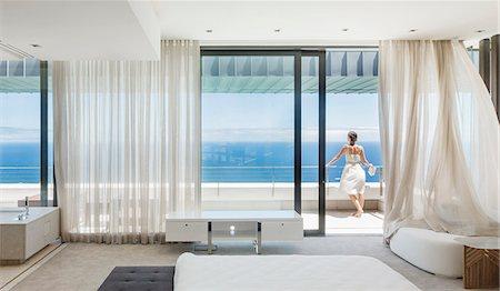 Woman on modern balcony overlooking ocean Stock Photo - Premium Royalty-Free, Code: 6113-07543305