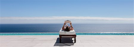 rich lifestyle - Woman relaxing on lounge chair at poolside overlooking ocean Stock Photo - Premium Royalty-Free, Code: 6113-07543315