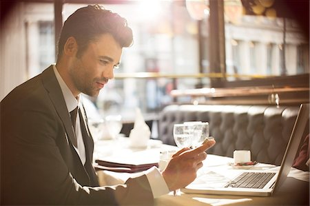 Businessman using laptop in restaurant Stock Photo - Premium Royalty-Free, Code: 6113-07543447