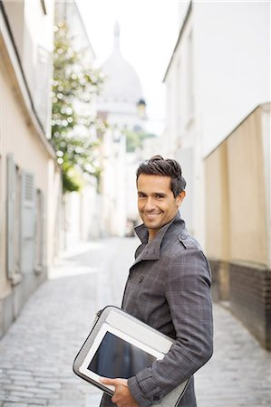 Businessman carrying digital tablet on city street Fotografie stock - Premium Royalty-Free, Codice: 6113-07543466
