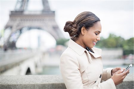 Businesswoman using cell phone near Eiffel Tower, Paris, France Stock Photo - Premium Royalty-Free, Code: 6113-07543477