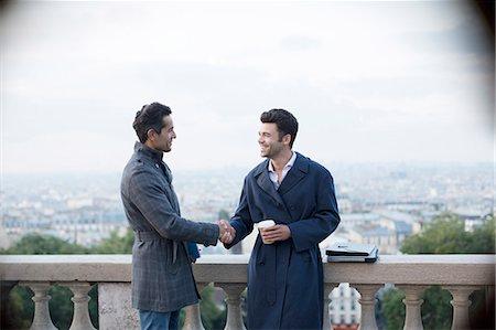 Businessmen shaking hands at railing overlooking Paris, France Stock Photo - Premium Royalty-Free, Code: 6113-07543479