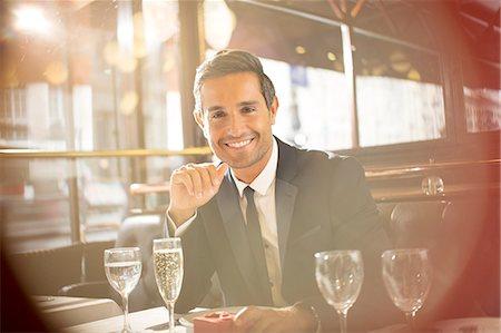 rich lifestyle - Businessman smiling at restaurant Stock Photo - Premium Royalty-Free, Code: 6113-07543493