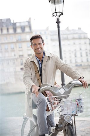 Businessman on bicycle along Seine River, Paris, France Stock Photo - Premium Royalty-Free, Code: 6113-07543498