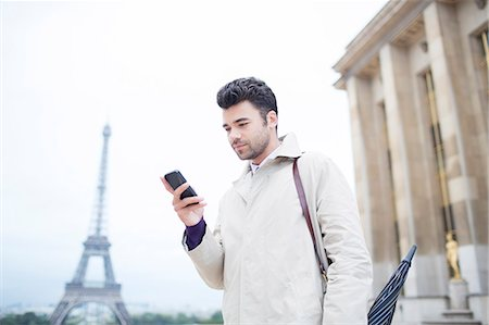 Businessman using cell phone by Eiffel Tower, Paris, France Stock Photo - Premium Royalty-Free, Code: 6113-07543404