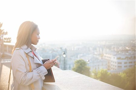 Businesswoman with cell phone overlooking Paris, France Stock Photo - Premium Royalty-Free, Code: 6113-07543413