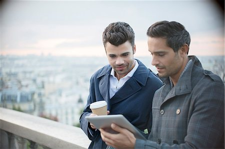 Businessmen using digital tablet with Paris, France in background Stock Photo - Premium Royalty-Free, Code: 6113-07543411