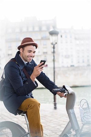 Businessman using cell phone on bicycle along Seine River, Paris, France Stock Photo - Premium Royalty-Free, Code: 6113-07543423