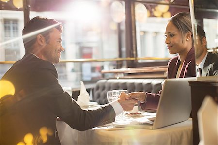 Business people shaking hands in restaurant Stock Photo - Premium Royalty-Free, Code: 6113-07543428