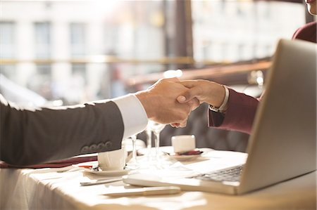 partnership - Business people shaking hands in restaurant Stock Photo - Premium Royalty-Free, Code: 6113-07543430