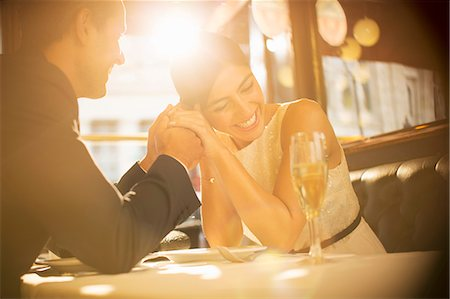 Couple holding hands in restaurant Stock Photo - Premium Royalty-Free, Code: 6113-07543540