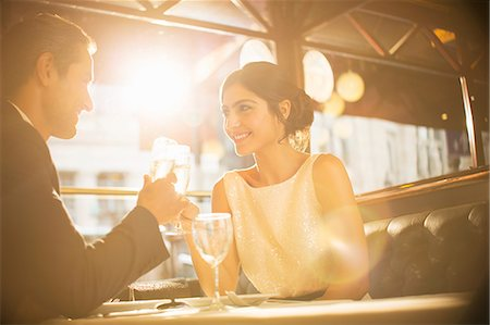 rich lifestyle - Couple toasting champagne flutes in restaurant Stock Photo - Premium Royalty-Free, Code: 6113-07543548