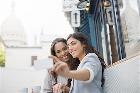 Friends taking self-portrait at sidewalk cafe near Sacre Coeur Basilica, Paris, France Stock Photo - Premium Royalty-Free, Code: 6113-07543565