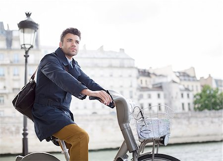 Businessman riding bicycle along Seine River, Paris, France Stock Photo - Premium Royalty-Free, Code: 6113-07543506