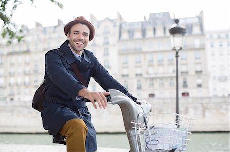 Businessman on bicycle along Seine River, Paris, France Stock Photo - Premium Royalty-Free, Code: 6113-07543509