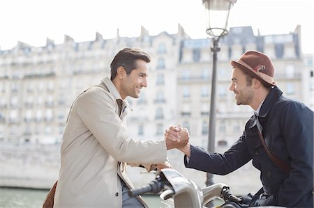 Businessmen shaking hands on bicycles along Seine River, Paris, France Stock Photo - Premium Royalty-Free, Code: 6113-07543513