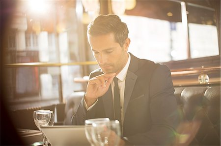 sit - Businessman using digital tablet in restaurant Stock Photo - Premium Royalty-Free, Code: 6113-07543518