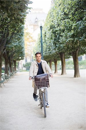 Businessman riding bicycle in park, Paris, France Stock Photo - Premium Royalty-Free, Code: 6113-07543526