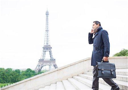 Businessmen on cell phone on steps near Eiffel Tower, Paris, France Stock Photo - Premium Royalty-Free, Code: 6113-07543528