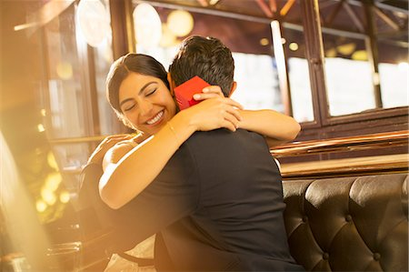 rich lifestyle - Woman with jewelry box hugging man in restaurant Stock Photo - Premium Royalty-Free, Code: 6113-07543645