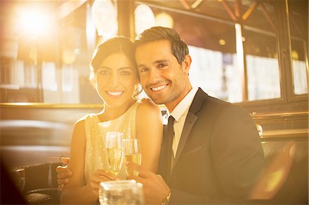 rich lifestyle - Couple toasting champagne flutes in restaurant Stock Photo - Premium Royalty-Free, Code: 6113-07543654
