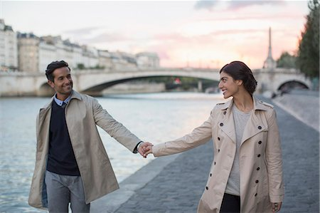 Couple holding hands along Seine River, Paris, France Stock Photo - Premium Royalty-Free, Code: 6113-07543658