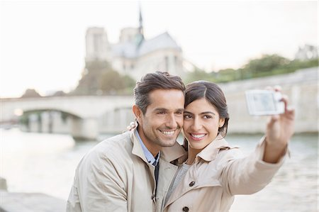Couple taking self-portrait along Seine River near Notre Dame Cathedral, Paris, France Stock Photo - Premium Royalty-Free, Code: 6113-07543672