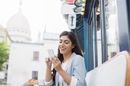 Woman using cell phone at sidewalk cafe near Sacre Coeur Basilica, Paris, France Stock Photo - Premium Royalty-Free, Code: 6113-07543614