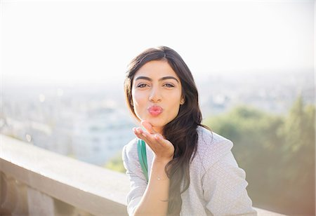 flirting - Woman blowing a kiss outdoors Stock Photo - Premium Royalty-Free, Code: 6113-07543616