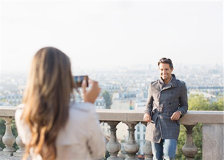 Woman photographing boyfriend with Paris in background Stock Photo - Premium Royalty-Free, Code: 6113-07543624