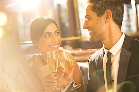 Well-dressed couple toasting champagne flutes in restaurant Stock Photo - Premium Royalty-Free, Code: 6113-07543628