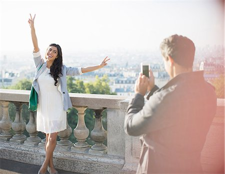 france - Man photographing girlfriend with city in background Stock Photo - Premium Royalty-Free, Code: 6113-07543633