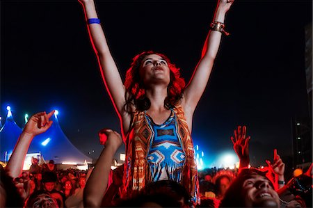 Cheering woman on man's shoulders at music festival Stock Photo - Premium Royalty-Free, Code: 6113-07564764