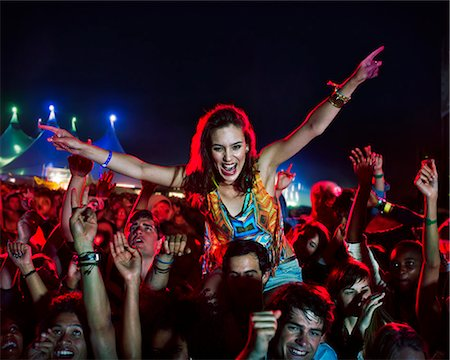 Cheering woman on man's shoulders at music festival Stock Photo - Premium Royalty-Free, Code: 6113-07564774